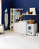 Blue laundry room with washing machine, dryer and an ironing board hanging on the wall