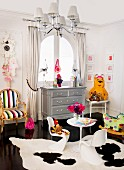 Postmodern-style child's bedroom; white plastic shell chairs on cowhide rug and neo-rococo armchair next to chest of drawers below window