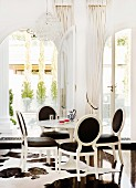 Postmodern dining area - white neo-rococo chairs with black upholstery in front of arched French windows with view onto terrace