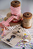 Key on labelled tag; ribbons and yarn on vintage wooden reels