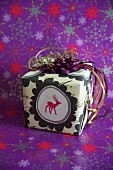 Wrapped Christmas present with reindeer motif standing on purple wrapping paper with pattern of stars