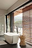 Moderne, freistehende Badewanne und Beistelltisch aus Rattan vor Fensterfront mit teilweise geschossenen Holz Jalousien
