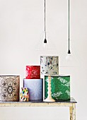 Assorted wallpapered lamp shades on a white, wood table under a hanging light with wire frames