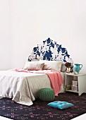 Doppelbett mit Tagesdecken vor Wand mit tapeziertem Kopfteil in barockem Stil und schlichtes Nachttischchen auf gemustertem Teppich mit Bodenkissen und Pouf