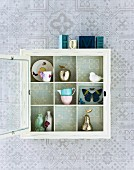 White lacquer, display cabinet hanging on a wallpapered wall with open glass door and view of the nick-nacks