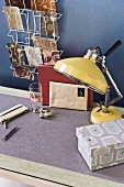 Retro, yellow metal table lamp and writing implements on a wallpapered table top in front of a blue wall with a metal, postcard holder hanging on it