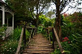 Romantic, old wooden bridge next to pavilion in lush, green garden