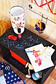 Bedside table with chalkboard top, lamp, children's drawings and toys
