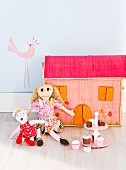 Rag dolls with colorful clothes in front of a doll's house