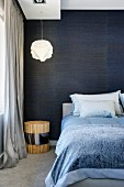 Double bed in front of shimmery, midnight blue, fabric wallpaper