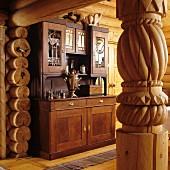 Gedrechselte Holzsäule im Durchgang und Blick auf antikes Küchenbuffet im Wohn-Esszimmer eines Blockhauses