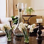 White flowers in glasses in front of antique carafe and candlesticks on wooden table