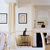 Animal ornament on round side table between open fireplace and classical columns in traditional, white living room