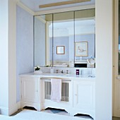 White washstand and triple mirror in niche in traditional bathroom with pastel-painted walls