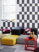 Red side table and floor cushions in a variety of colors in front of a wall with a black and white, geometric pattern
