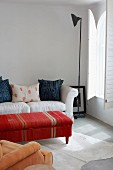 Coffee table covered in ethnic fabric in front of a light sofa and retro floor lamp in a minimalist room with interior shutters at the arched window