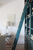 Blue, lacquer ladder in front of a bookcase and table lamp with earth tone lamp shade on a modern side table by the wall