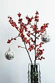 Mosaic mirrored disco balls hanging on festive holly branches with red berries