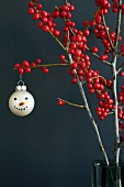 Christmas tree bauble painted with snowman's face hanging on decorative branch of holly