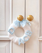 White wool wreath decorated with letters hanging on a door