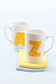 Two white cups printed with the letters A and Z