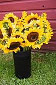 Ein Strauss Sonnenblumen in Vase auf Rasen im Freien
