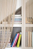 String curtain in front of fitted shelving below staircase