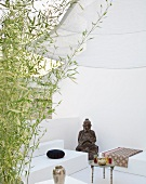 Seating area as continuous, white spatial sculpture half hidden behind bamboo with figure of Buddha and small Oriental tea table