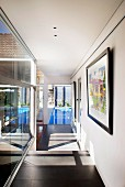 Sunny corridor with view of swimming pool; framed artworks on wall