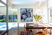 Glass-walled dining room with view of pool in garden and picture of grapes on back wall