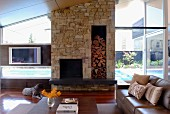 High-ceilinged interior with stone chimney breast in contemporary glass house