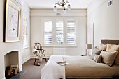 Pale bedroom with stucco friezes and exterior louver blinds; bed with upholstered headboard and bed linen in shades of beige and clothing on Shaker-style chair