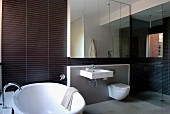 Designer bathroom with shower, anthracite strip tiles and large mirrored element