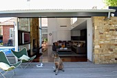 Butterfly chairs and dog on wooden terrace with view into high-ceilinged interior of contemporary house making much use of glass and stone