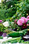Arrangement of vegetables and colourful bouquet of dahlias on table in garden