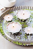 Candle arrangement with cake moulds, decorative pebbles and glory-of-the-snow flowers
