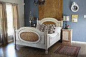 Antique double bed in front of wall hanging on blue-painted wall in elegant, vintage bedroom