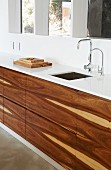 Designer kitchen counter with white worksurface and base unit fronts of tropical wood