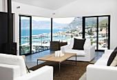 Wohnraum mit Panoramablick auf bergige Meeresküste - Couchtisch mit Holzplatte und weisse Polstersofagarnitur