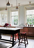 Country-house kitchen with sash windows and retro lamps; wooden stools around heavy table with marble top in middle