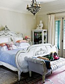 Ornate bed and recamier bench below chandelier