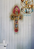 Chandelier and kitsch version of Christian cross on wood-clad wall above toilet