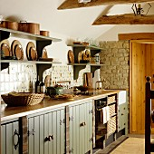 Wall-mounted shelves above kitchen counter with base units in rustic kitchen