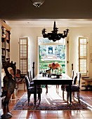 Dining table in front of open terrace doors with interior, folding shutters; stylised, painted, wooden bird statue