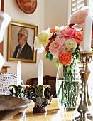 Kerzenhalter aus bemalter Keramik als strampelnde Zebrafigur und Rosenstrauss auf einem Esstisch; Männerportrait im Hintergrund