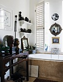 Collection of busts, figurines and mirrors on console table and wall-mounted shelves over bathtub