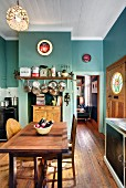Turquoise, traditional-style kitchen with pots and pans hanging over wooden cabinet