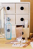 Small chest of drawers full of ribbons behind bluish vintage bottle