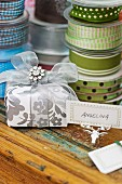 Wrapped present with name tag on silver moose-antler ornament in front of stacked spools of ribbon