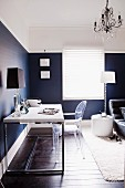 Home office in bedroom - modern desk, plexiglass chair and table lamp against wall in elegant blue and white